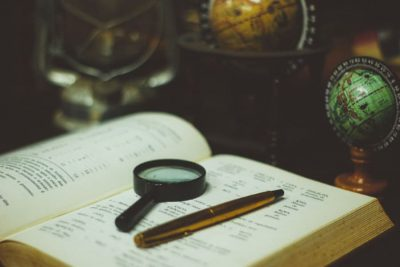 a magnifier and a pen laid on a dictionary representing a translation technique