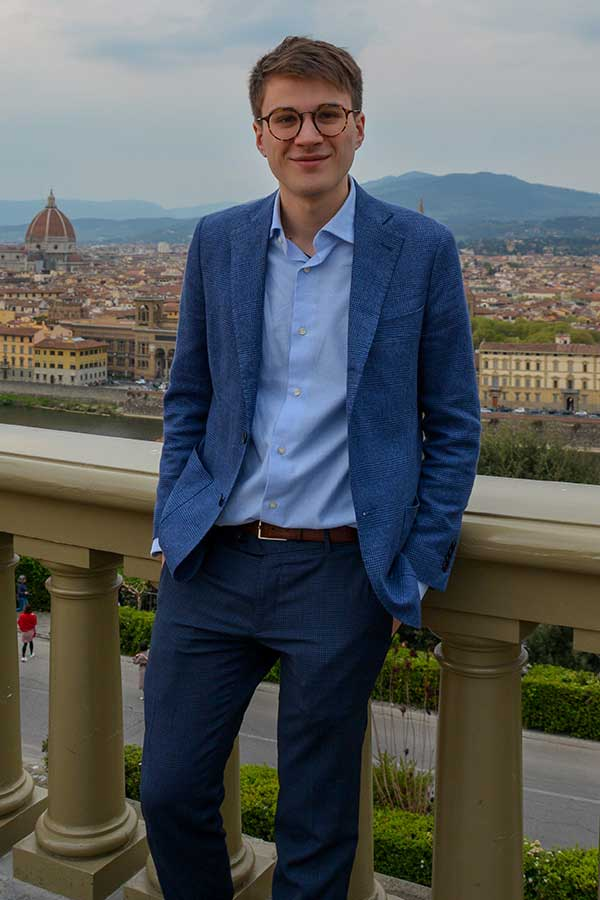 arrigo in a blue suit standing in piazza michelangelo of florence with a view
