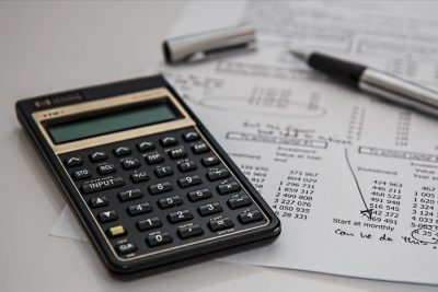 a calculator and a pen with financial papers on a desk